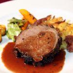 Lamsbout met roseval aardappelen en garnituur van geblakerde groenten en koolraap